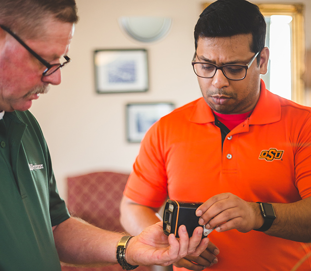 Anthony Bivings, unit manager of Weyerhaeuser's Idabel sawmill, presents the camera to Instrumentation instructor Geeth Bagusetty.