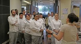 Students from the School of Culinary Arts listens as Carla Meneses, owner of Que Gusto, talks about starting her restaurant through Kitchen 66.