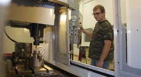 Student operating manufacturing equipment