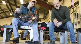 A student in the School of Construction Technologies works with a representative from Wolverine to get just the right fit for his free pair of Wolverine work boots.