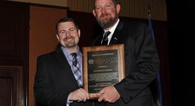 Brandon Cheney, left, is presented with the Project Manager of the Year award by AGC of Oklahoma President Matt Parker.