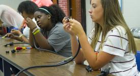 A group of eighth through 10th graders work on making their own extension cords as part of the Emerging & Converging Summer Academy.